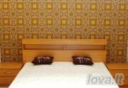 Miegamojo lova su lentynomis